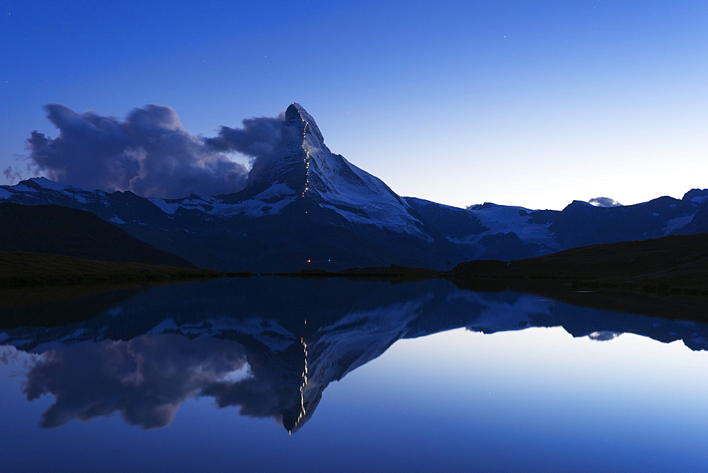 The Matterhorn, 4478m, illuminated in honour of the 150th anniversary of the first ascent, Stellisee lake, Zermatt, Valais, Swiss Alps, Switzerland, Europe