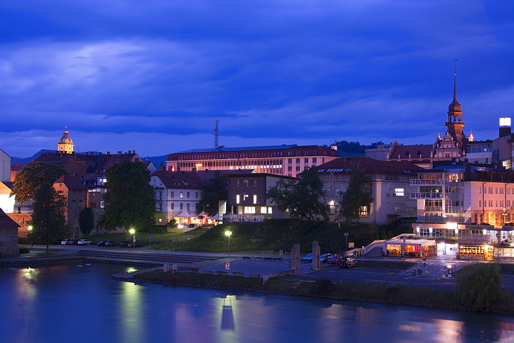 A cityscape of Maribor along the Draca river at night, Slovenia.