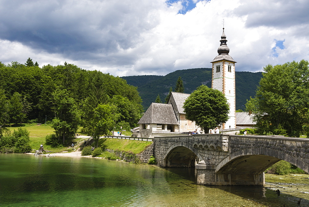 The church of St. John the Baptist and the stone bridge on Lake Bohinj, Slovenia, Europe