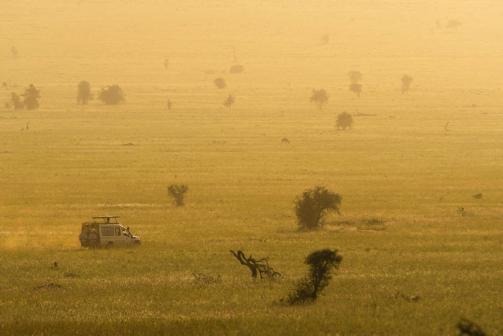 A safari vehicle driving across the plains of Tsavo at sunset, Kenya, East Africa, Africa