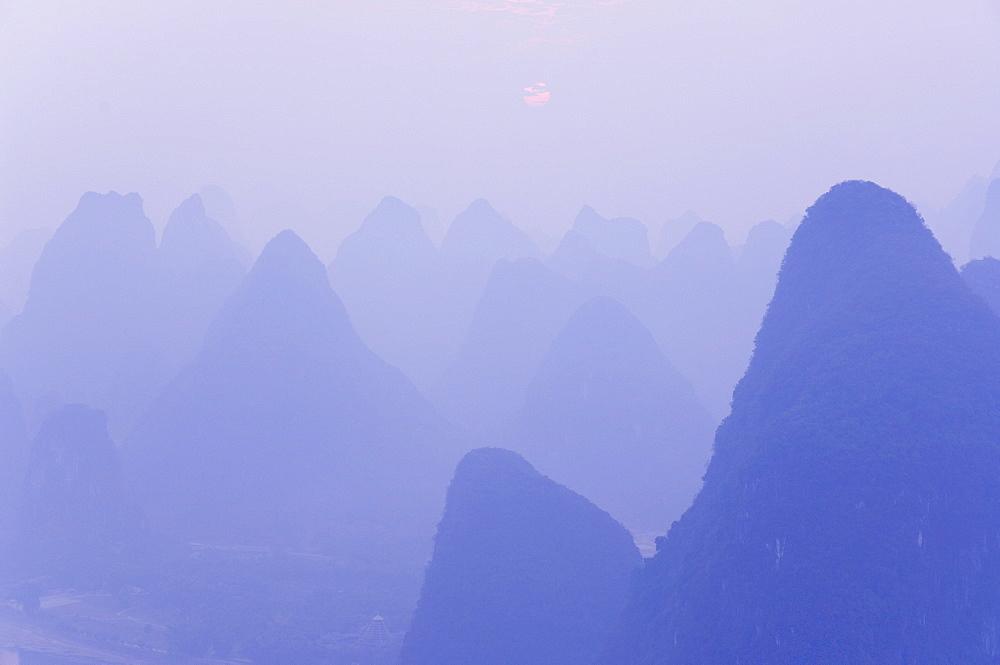 Karst landscape, haze and rising sun, Yangshuo, Guangxi Province, China, Asia - 756-24