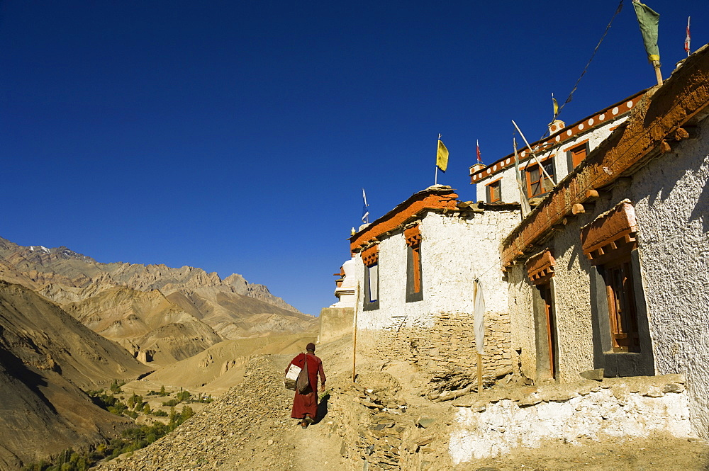 Monk walking past Lamayuru gompa (monastery), Lamayuru, Ladakh, Indian Himalayas, India, Asia