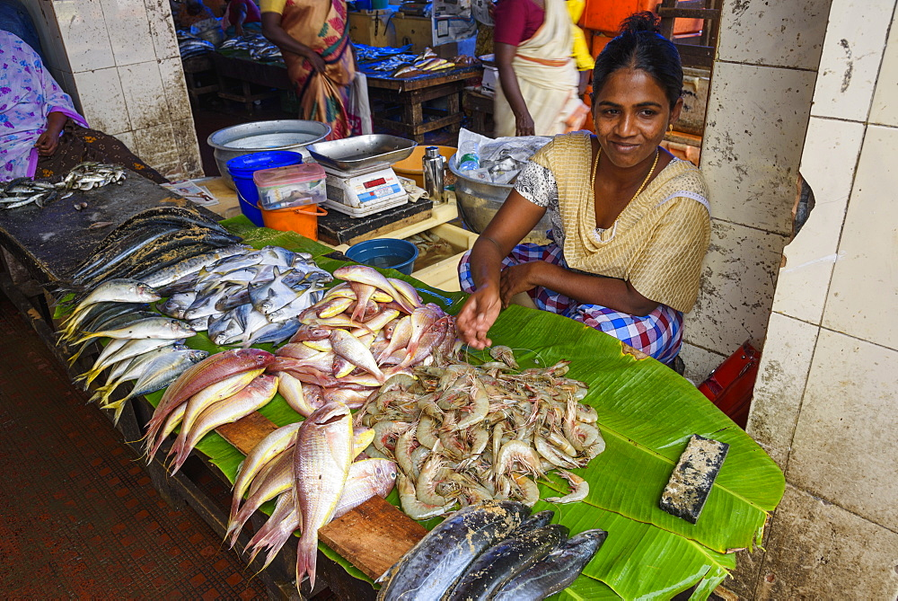 Woman selling fresh seafood at street market in Trivandrum, India