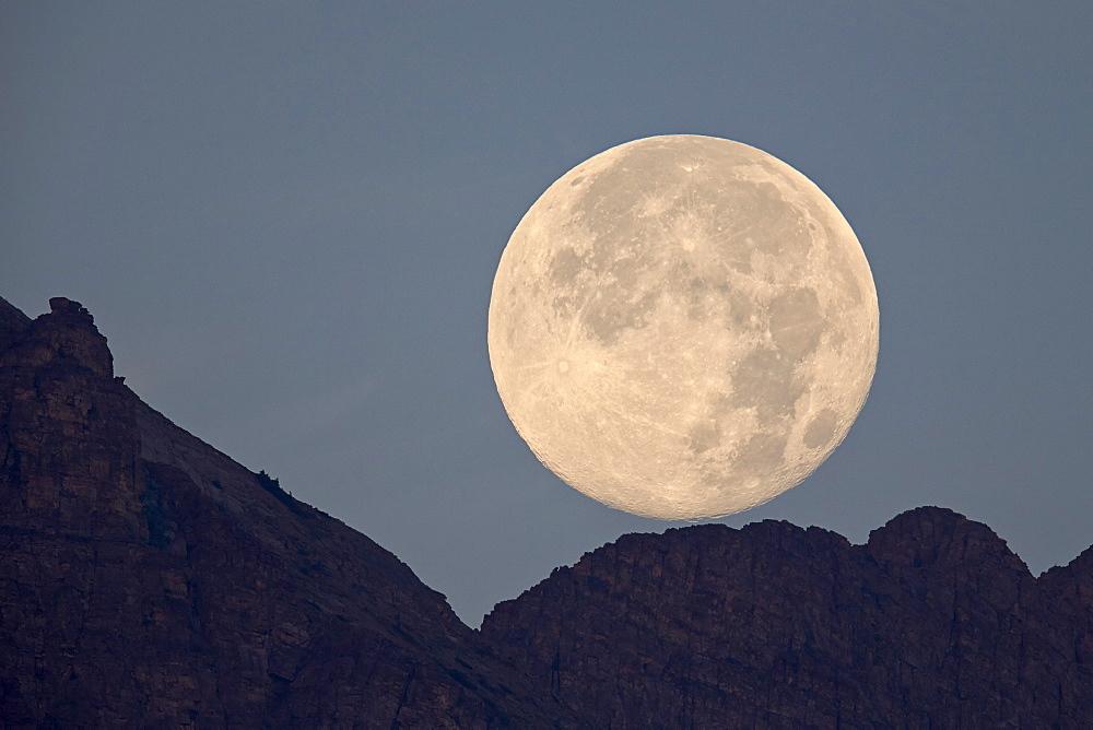 Full moon setting above a ridge, Glacier National Park, Montana, United States of America, North America