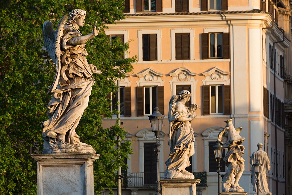 Angel statues on Ponte Sant' Angelo with grand house behind, Rome, Lazio, Italy, Europe