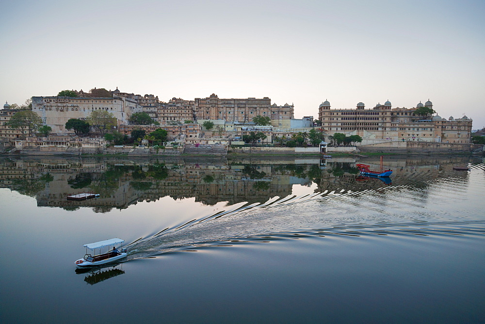 A water taxi passing the City Palace reflected in the still dawn waters of Lake Pichola, Udaipur, Rajasthan, India, Asia