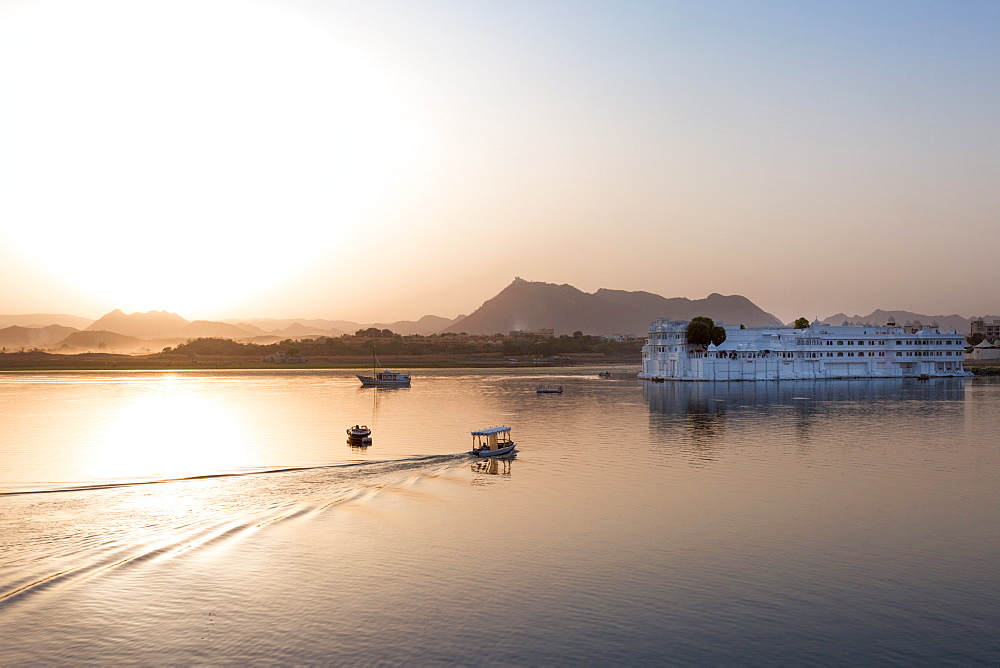 Boat going out to Lake Palace Hotel at dusk, the hotel is situated in the middle of Lake Pichola, in Udaipur, Rajasthan, India, Asia