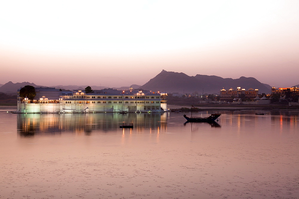 Perfect reflection of Lake Palace Hotel at dusk, situated in the middle of Lake Pichola, in Udaipur, Rajasthan, India, Asia