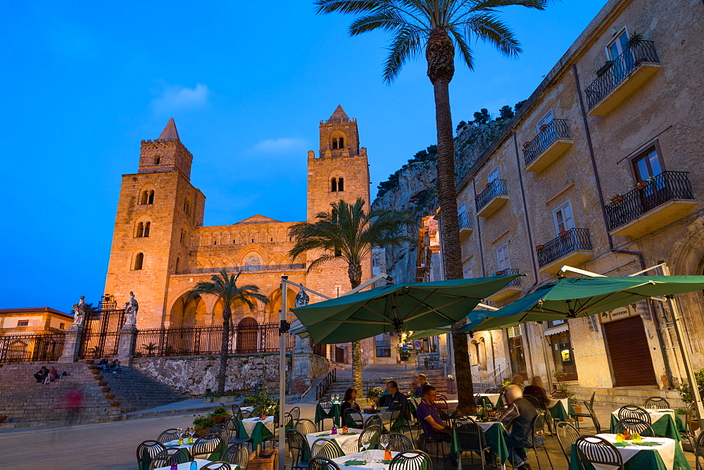 People dining in Piazza Duomo in front of the Norman Cathedral of Cefalu illuminated at night, Cefalu, Sicily, Italy, Europe
