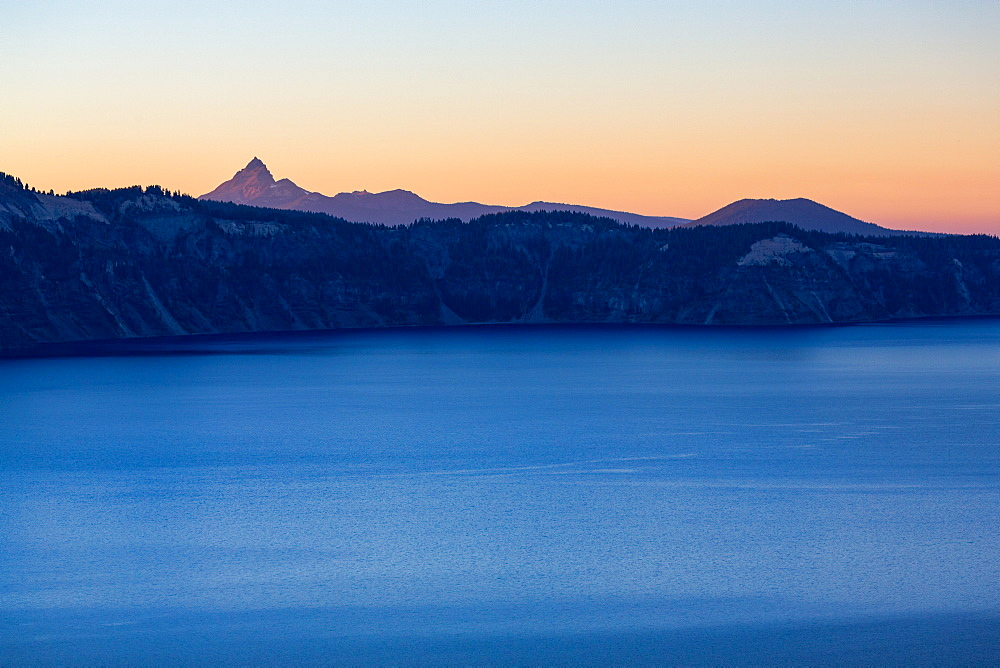 Dusk over the still waters of Crater Lake, with Mount Thielsen. It is the deepest lake in the USA, part of the Cascade Range