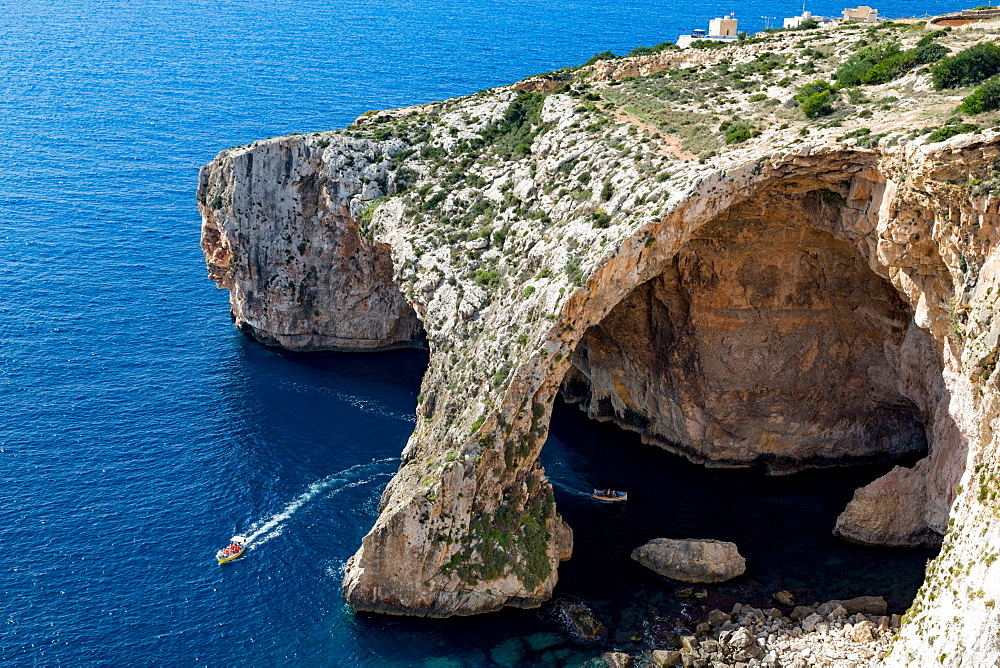 Boats of tourists visiting the dramatic natural arch at the Blue Grotto, Malta, Mediterranean, Europe