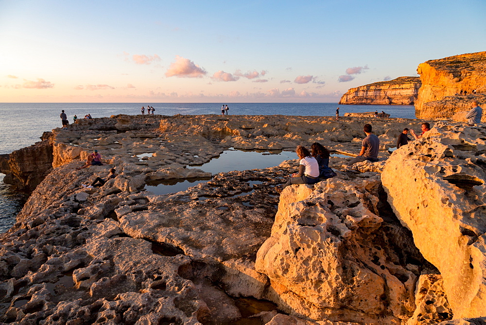 People enjoying sunset at Dwejra Bay on the rugged Gozo coast, Malta, Mediterranean, Europe
