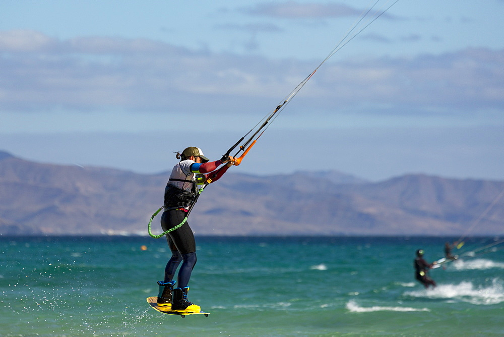 Man jumping whilst kiteboarding off the Playa de La Barca, Costa Calma, on the volcanic island of Fuerteventura, Canary Islands, Spain, Atlantic, Europe - 785-2253