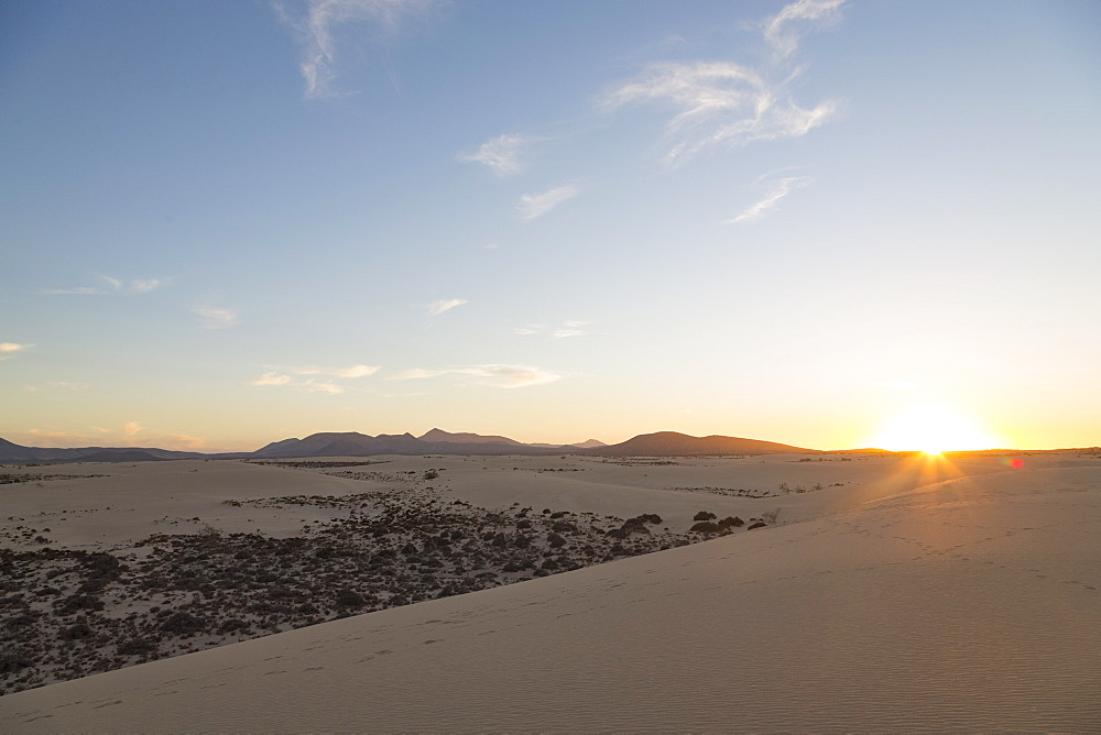 The sun setting over the dramatic Dunas de Corralejo on the volcanic island of Fuerteventura with mountains beyond, Fuerteventura, Canary Islands, Spain, Europe - 785-2278