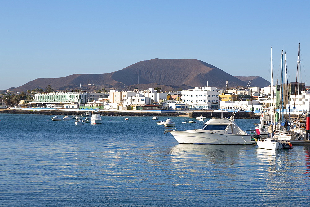 The harbour at Corralejo on the island of Fuerteventura with a volcano in the distance, Fuerteventura, Canary Islands, Spain, Atlantic, Europe - 785-2280