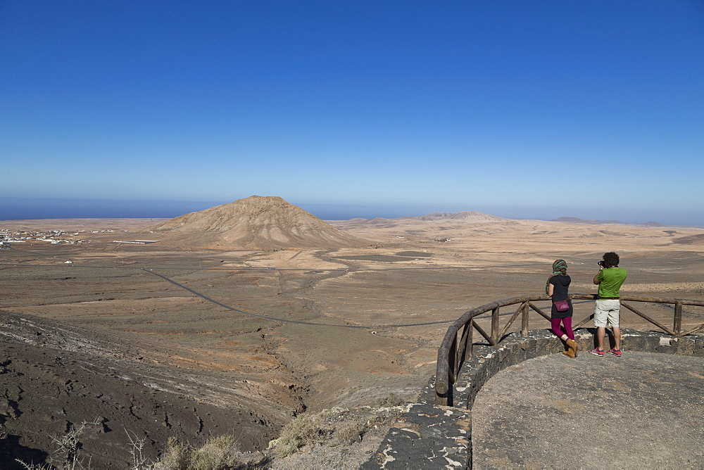 Two people at Mirador de Vallebron looking towards Tindaya volcano on the island of Fuerteventura, Canary Islands, Spain, Atlantic, Europe - 785-2289