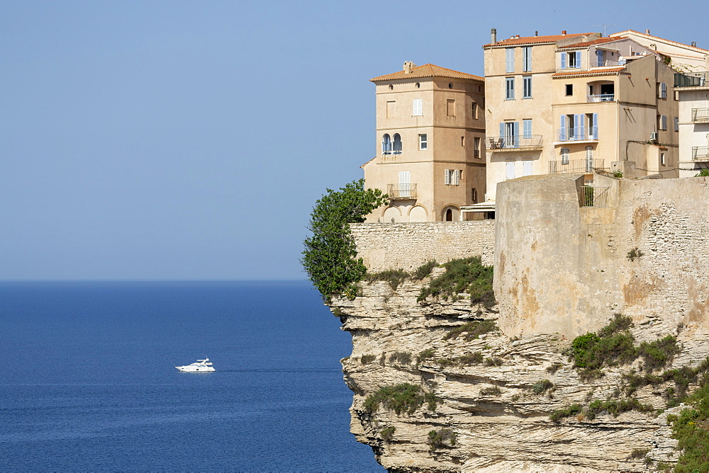 The Citadel and old town of Bonefacio perched on rugged cliffs with boat in the Mediterranean sea - 785-2354