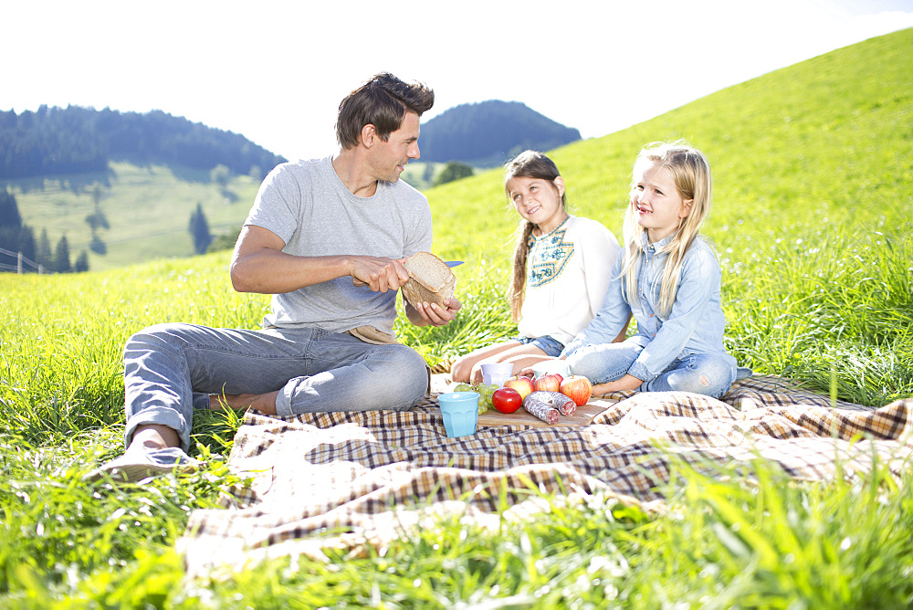 Fathers With Daughters Enjoying Countryside Picnic Together