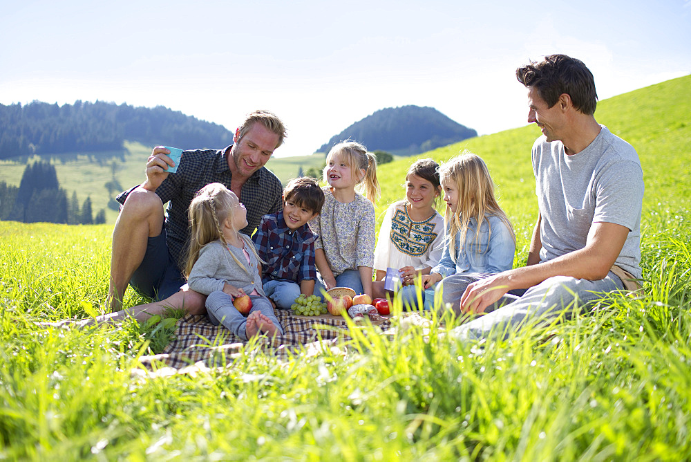 Fathers With Children Enjoying Countryside Picnic Together