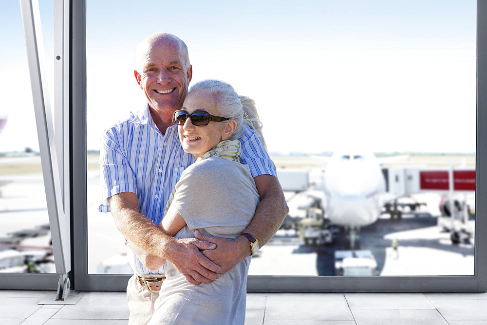 Portrait Of Senior Couple In Airport Departure Lounge