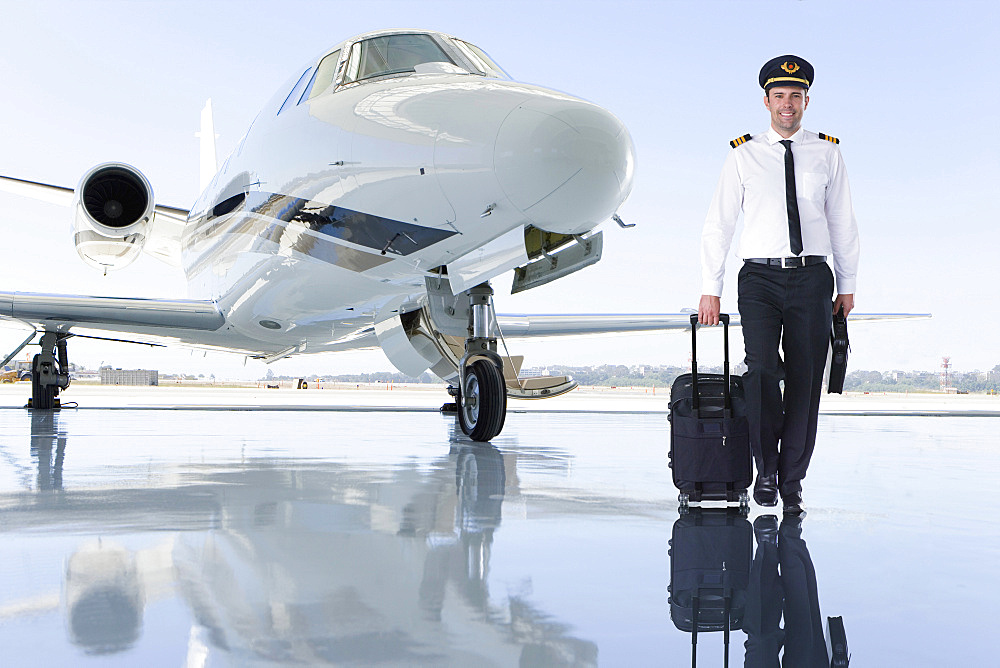 Pilot Of Private Jet Standing By Aircraft In Hangar