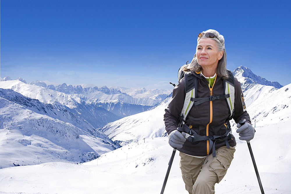 Mature Woman Hiking Through Snow Covered Mountains
