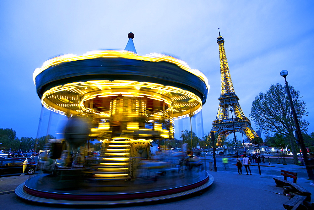 Carousel below the Eiffel Tower at twilight, Paris, France, Europe