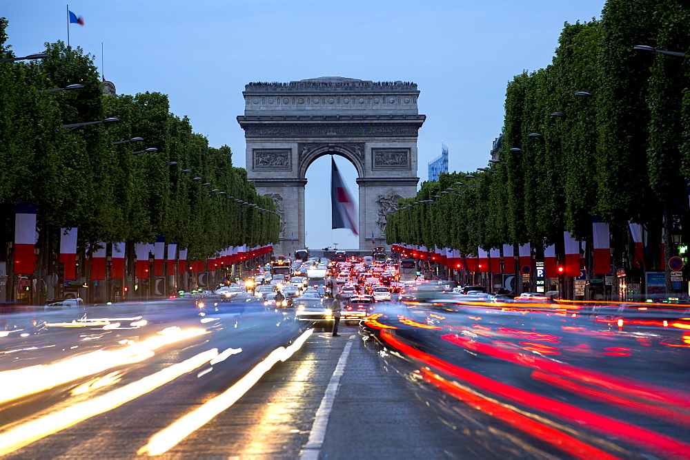 View down the Champs Elysees to the Arc de Triomphe, illuminated at dusk, Paris, France, Europe