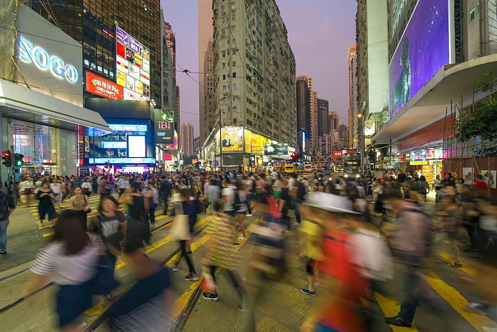 Pedestrians and traffic at a busy road crossing in Causeway Bay, Hong Kong Island, Hong Kong, China