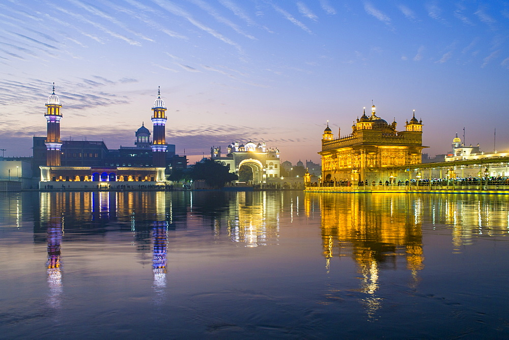 The Golden Temple (Harmandir Sahib) and Amrit Sarovar (Pool of Nectar) (Lake of Nectar), illuminated at dusk, Amritsar, Punjab, India, Asia
