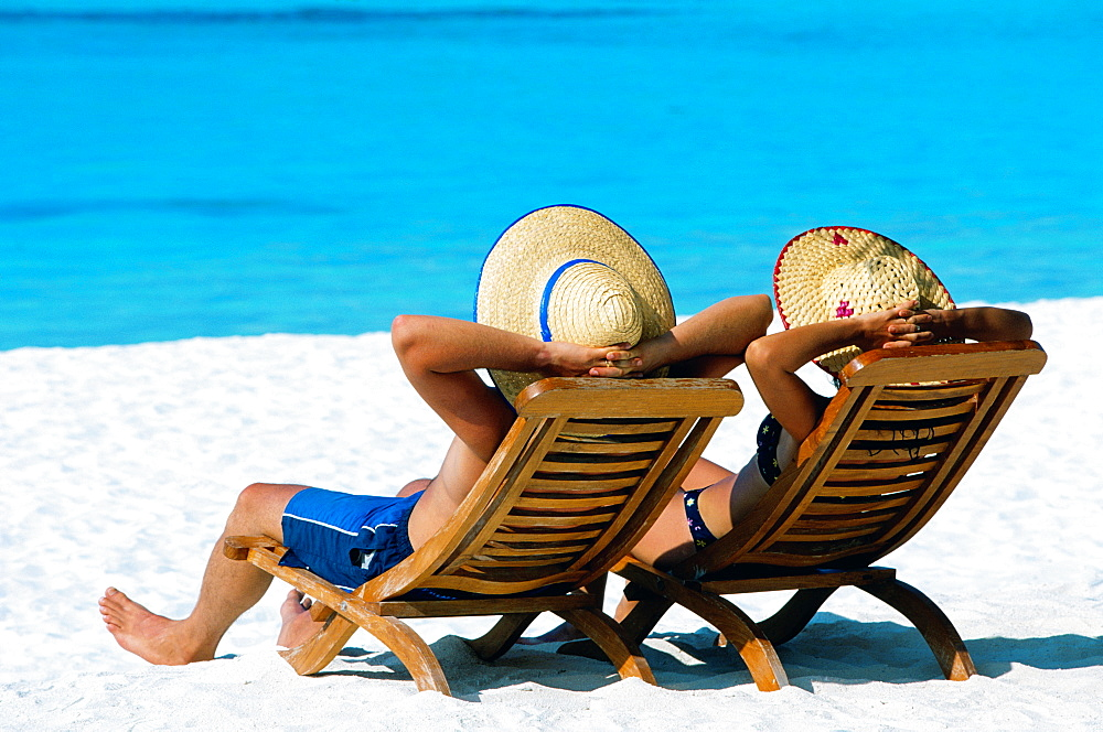 Couple lying in deck chairs on beach, The Maldives, Indian Ocean, Asia