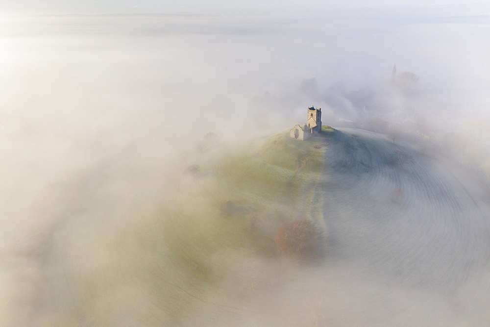 Aerial view by drone of St. Michael's Church on Burrow Mump, surrounded by a blanket of mist, Burrowbridge, Somerset, England, United Kingdom, Europe