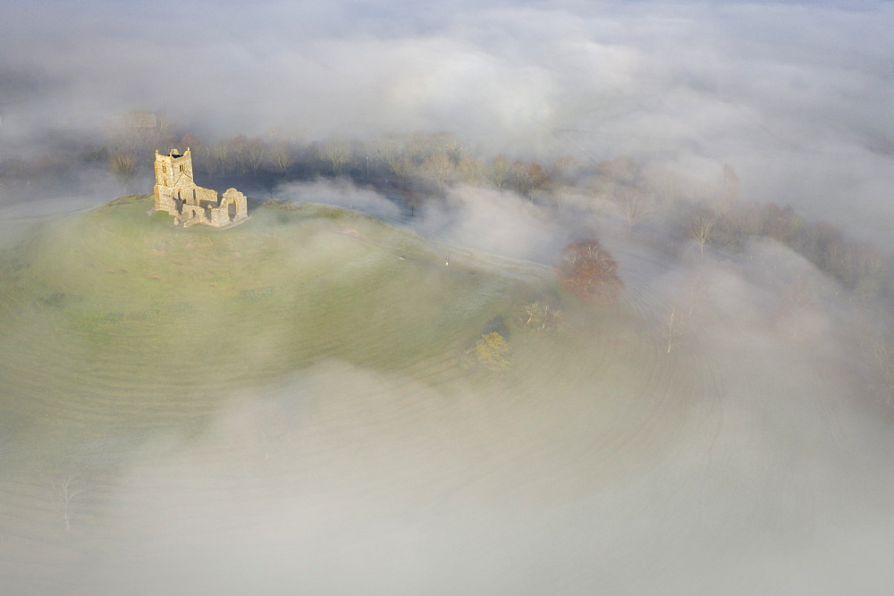 Aerial image of St Michael???s Church on Burrow Mump, surrounded by a blanket of mist. Burrowbridge, Somerset, England. Winter (December) 2019.