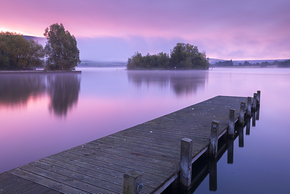 Pink sunrise over Llangorse Lake in the Brecon Beacons National Park, Powys, Wales, United Kingdom, Europe