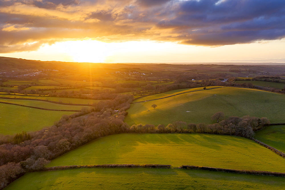 Aerial vista by drone of rolling countryside at sunset in spring, Devon, England, United Kingdom, Europe