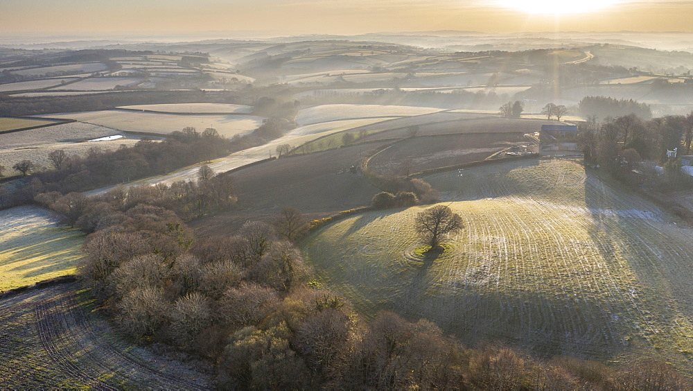 Aerial vista by drone of frosty rolling countryside at dawn in spring, Devon, England, United Kingdom, Europe - 799-4022