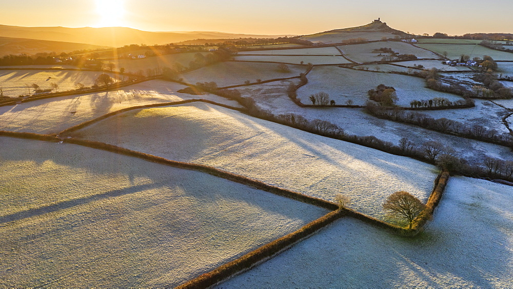 View by drone of frosty winter sunrise over Dartmoor countryside near Brentor, Devon, England, United Kingdom, Europe