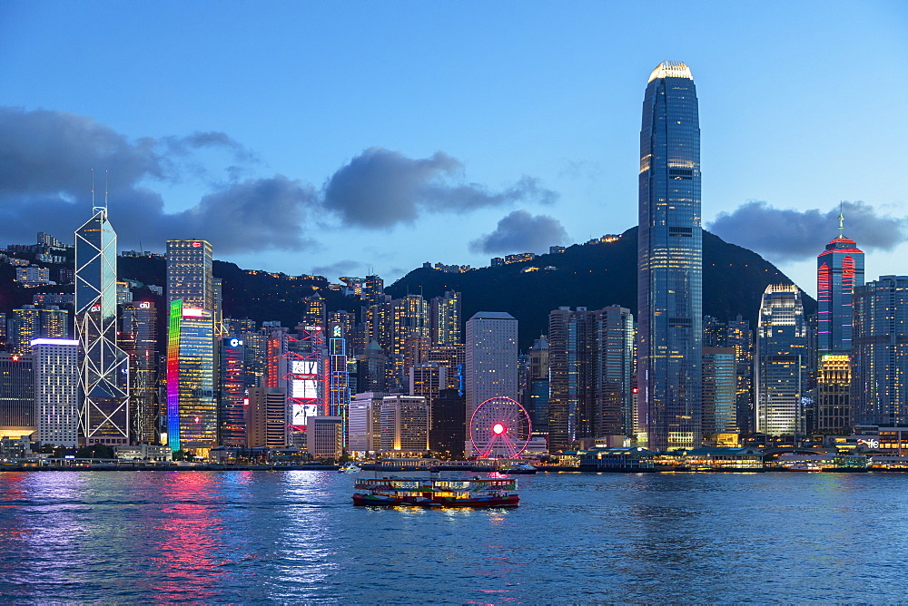 Star Ferry in Victoria Harbour and skyline of Hong Kong Island at dusk, Hong Kong, China, Asia