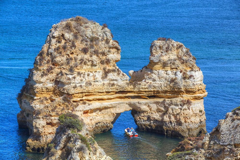 Tourist boat manoeuvering through the Grotos of Ponta da Piedade, Algarve, Portugal, Europe