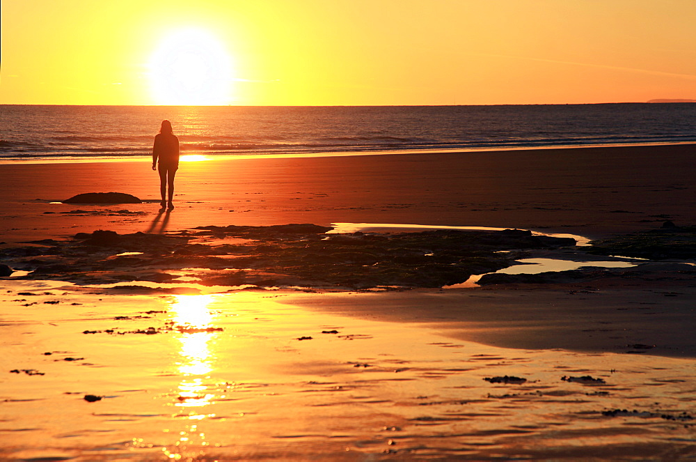 A woman walks on Southerndown beach, Ogmore, South Wales