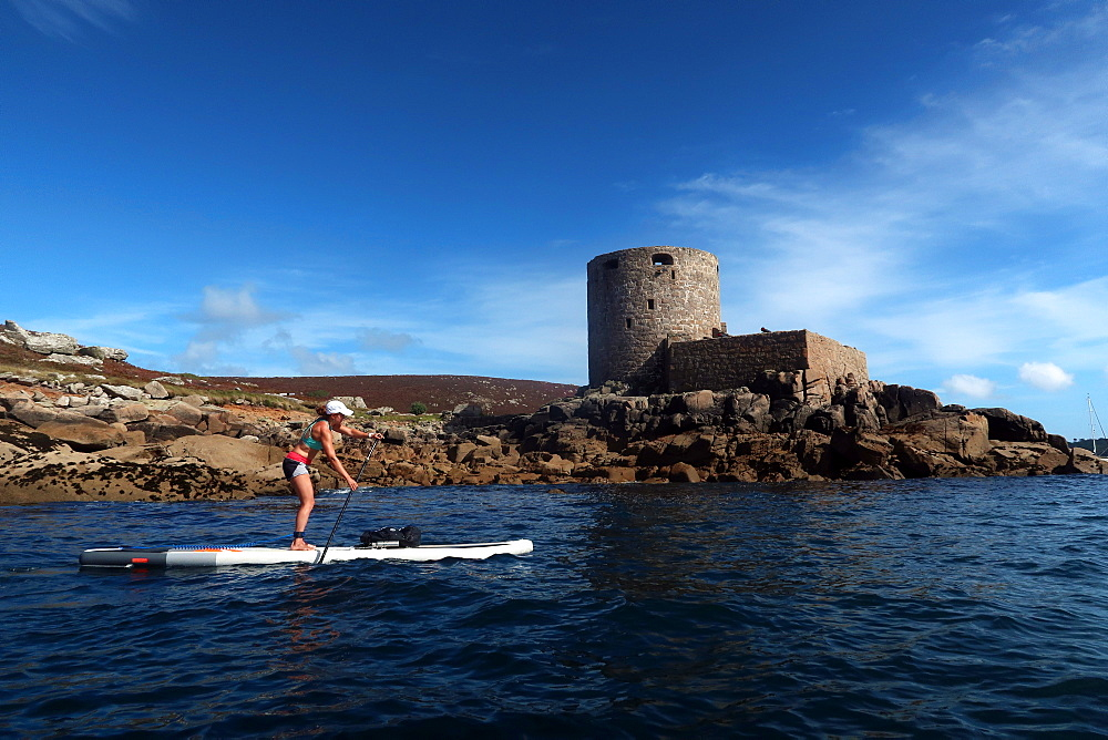 Paddle boarder under Cromwell's Castle, a castle built during the English Civil War on the west coast of Tresco, Isles of Scilly - 802-583