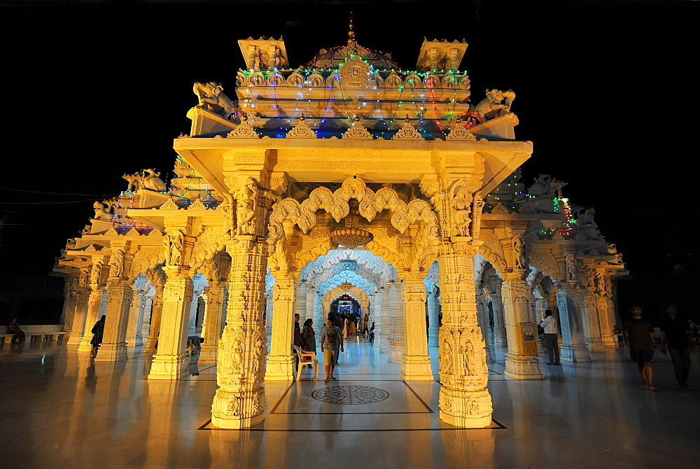 Entrance to the beautiful white marble Swaminarayan Temple, illuminated for evening prayers, Mandvi, Gujarat, India, Asia