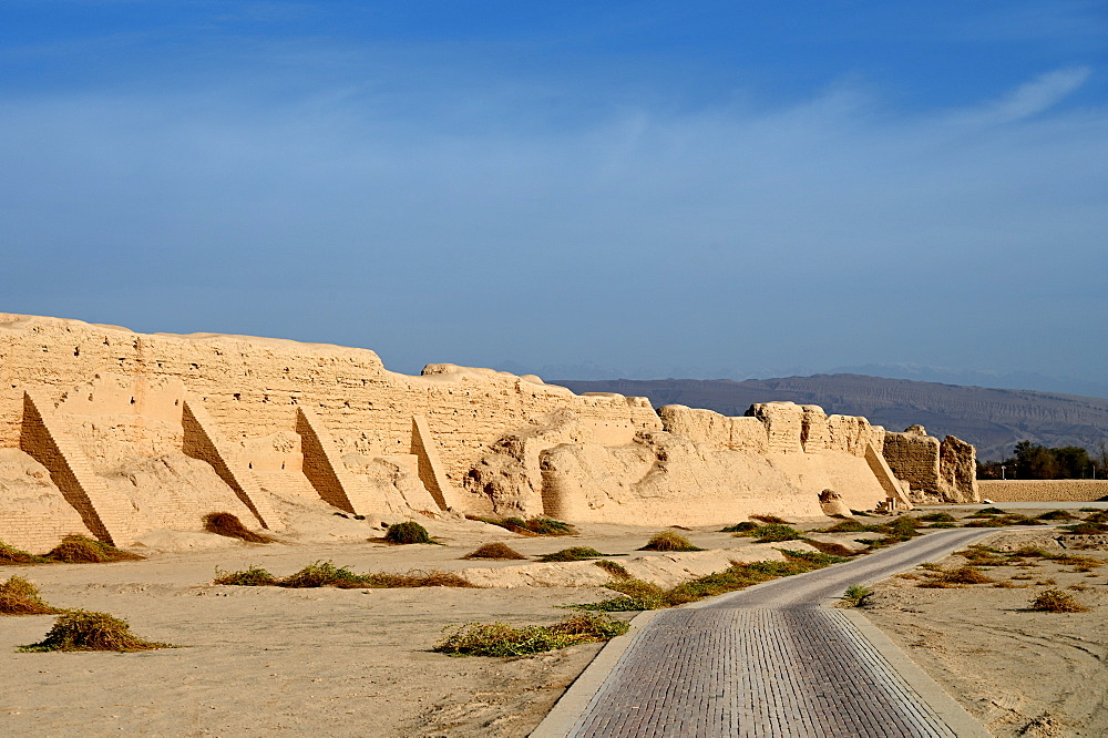 Road past ruined city wall of ancient Silk Road city of Gaochang, Taklamakan desert, Xinjiang, China, Asia