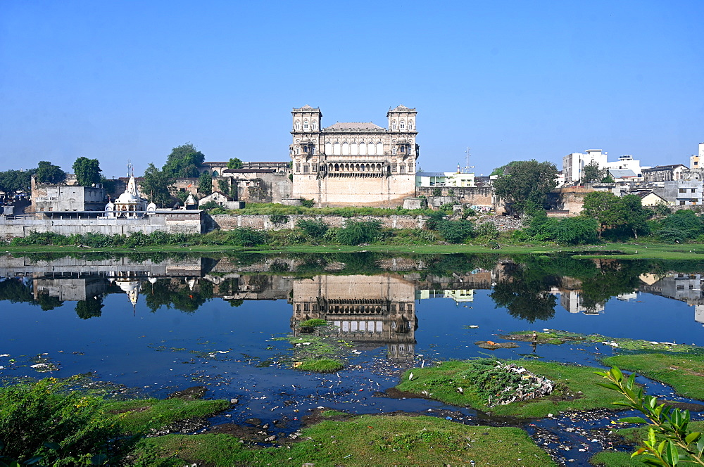 The 18th century Naulakha Palace facade reflected in the still waters of the Gondal River, Gondal, Gujarat, India, Asia