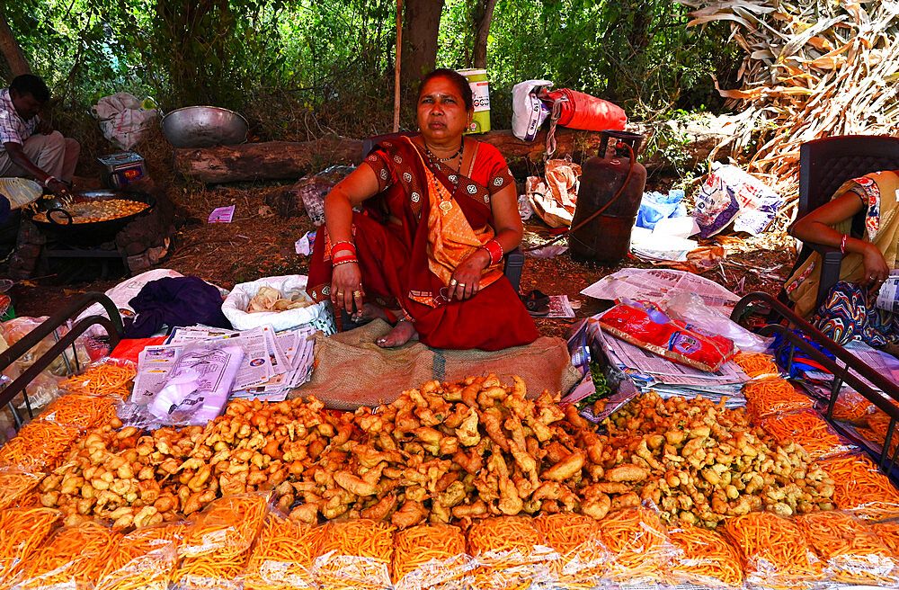 Adivasi woman selling freshly cooked pakora at traditional village fair celebrating Holi festival, Gujarat