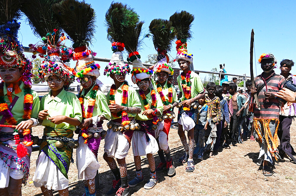 Adavasi tribal men, faces and bodies decorated, wearing ornate headgear, dancing to celebrate Holi festival, Kavant, Gujarat