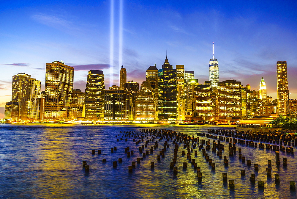 Lower Manhattan skyscrapers including One World Trade Center from across the East River at night, with light beams from the Tribute in Light 9/11 Memorial, New York City, New York, United States of America, North America
