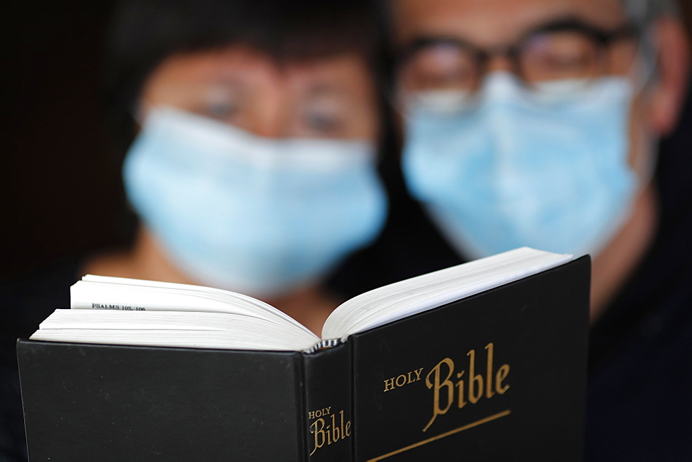 Man and woman reading the bible with a disposable mask to avoid contagious coronavirus (COVID-19), France, Europe
