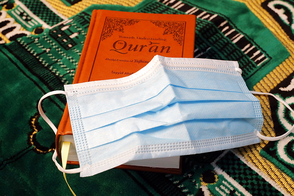 Religion and coronavirus (COVID-19) Quran and disposable surgical mask, Haute-Savoie, France, Europe