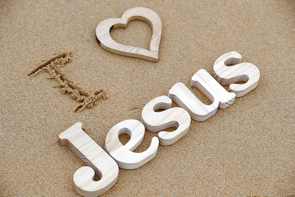 Wooden letters forming the word JESUS with heart on a background of beach sand, I love Jesus, Christian symbol, Vietnam, Indochina, Southeast Asia, Asia